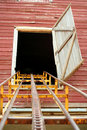 Hay Conveyor Leading Up To A Barn Door Stock Images - 15086034