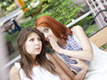Two Girls Gossiping On Bench At Garden. Royalty Free Stock Images - 15154929