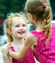 A Little Girl Smiles Adoringly At Her Sister Royalty Free Stock Image - 15683146