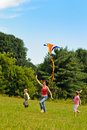 Young Woman And Children Flying A Kite Stock Photos - 16306423