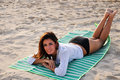 Young Smiling Woman Laying On Towel At The Beach Royalty Free Stock Image - 16716726