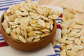 Toasted Pumpkin Seeds Overflowing A Wooden Bowl Royalty Free Stock Image - 16845206