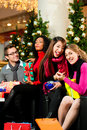 Friends Christmas Shopping With Presents In Mall Stock Photo - 17251210