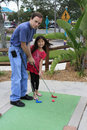 Little Asian Girl Playing Mini Golf With Dad Stock Photos - 17633853