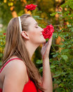 Woman In Her Garden Sniffing At The Roses Stock Images - 18209714