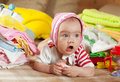 Baby Girl With Heap Of Baby S Wear Stock Image - 18358801
