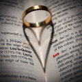 Ring Casting A Heart-shaped Shadow In A Book. Royalty Free Stock Image - 18799986