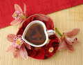 Red Cup Of Tea In The Form Of Heart With Pink Orchids Over Straw Royalty Free Stock Image - 2052516