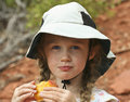 A Little Girl In A White Hat Eating A Peach Stock Photos - 20767763