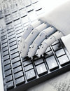 A Wooden Hand Is Typing Stock Photo - 21075400