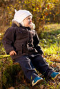 Cute Child Sitting On A Stump Stock Image - 23550241