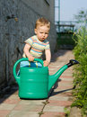 Young Boy Playing With The Watering Can Royalty Free Stock Images - 23600489
