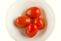 Four Marinated Tomatoes On A White Plate Stock Photography - 23954662
