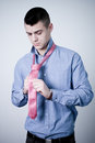 Business Man Binding His Pink Tie Royalty Free Stock Images - 23960599