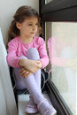 Girl Sits On Windowsill And Looks Out Window Stock Images - 23997144