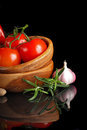 Tomatoes And Garlic In Wooden Plate On Black Backg Stock Photos - 24059613