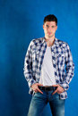 Young Man With Plaid Shirt Denim Jeans In Blue Royalty Free Stock Photography - 24165087