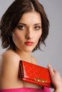Young Beautiful Woman With A Red Purse Royalty Free Stock Photo - 24312775
