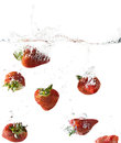 Red Strawberries Falling Into Water Royalty Free Stock Image - 24390596