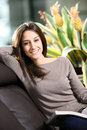 Young Woman Lying On A Sofa Reading A Magazine. Stock Images - 24480584