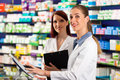 Pharmacist With Assistant In Pharmacy Royalty Free Stock Photos - 24651778