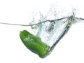 Green Pepper Falling Into Water Over White Stock Image - 25177991