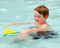 Young Boy Plays With Toy Boat While In Pool Royalty Free Stock Photography - 25457777