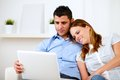Lovely Couple Smiling And Reading On Laptop Stock Images - 25502734
