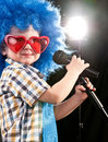 Boy Sings Into A Microphone Royalty Free Stock Images - 25571399