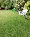 Green Lawn With Flowers And Lawn Chairs Royalty Free Stock Image - 25582556