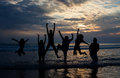 Big Family Jumping On The Beach At Dusk Royalty Free Stock Images - 25599939