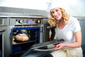 Pretty Baker Opening An Oven Door Stock Images - 25621664
