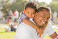 Mixed Race Father And Son Playing Piggyback Royalty Free Stock Image - 25651396