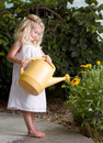 Young Girl Watering Flowers Royalty Free Stock Images - 25677779