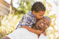 Mixed Race Father And Son Playing Piggyback Royalty Free Stock Image - 25698846