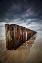 Old Timber Sea Barrier With Cloudy Sky Royalty Free Stock Photography - 25846827
