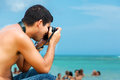 Hispanic Photographer At The Beach Royalty Free Stock Images - 25851169