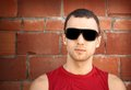Young Man In Black Sunglasses Over Old Brick Wall Stock Photography - 25868012