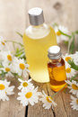 Essential Oil And Camomile Flowers Royalty Free Stock Photography - 25888807