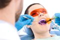 Dentist Uses Photopolymer Lamp To Cure Teeth Royalty Free Stock Photos - 25920828