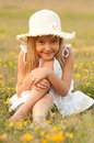 Cute Little Girl Sitting On The Meadow Stock Photography - 26127542