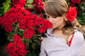 Young Woman In Flower Garden Smelling Red Roses Royalty Free Stock Photos - 26161718