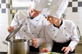 Two Chefs In Team In Hotel Or Restaurant Kitchen Royalty Free Stock Photography - 26166567