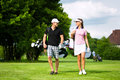 Young Sportive Couple Playing Golf On A Course Stock Photo - 26166790
