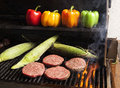 Grilling Hamburgers And Corn Royalty Free Stock Images - 26201059
