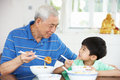 Chinese Grandfather And Grandson Eating Meal Stock Photography - 26245742