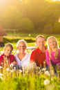 Happy Family Sitting In Summer Meadow Royalty Free Stock Photography - 26869217