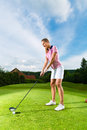 Female Golf Player On Course Doing Golf Swing Royalty Free Stock Photography - 26869297