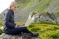Young Blond Woman Sits With A Laptop On A Stone Stock Photo - 26945660