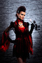 A Young Brunette Lady Vampire Holding A Rose Stock Photo - 27035100